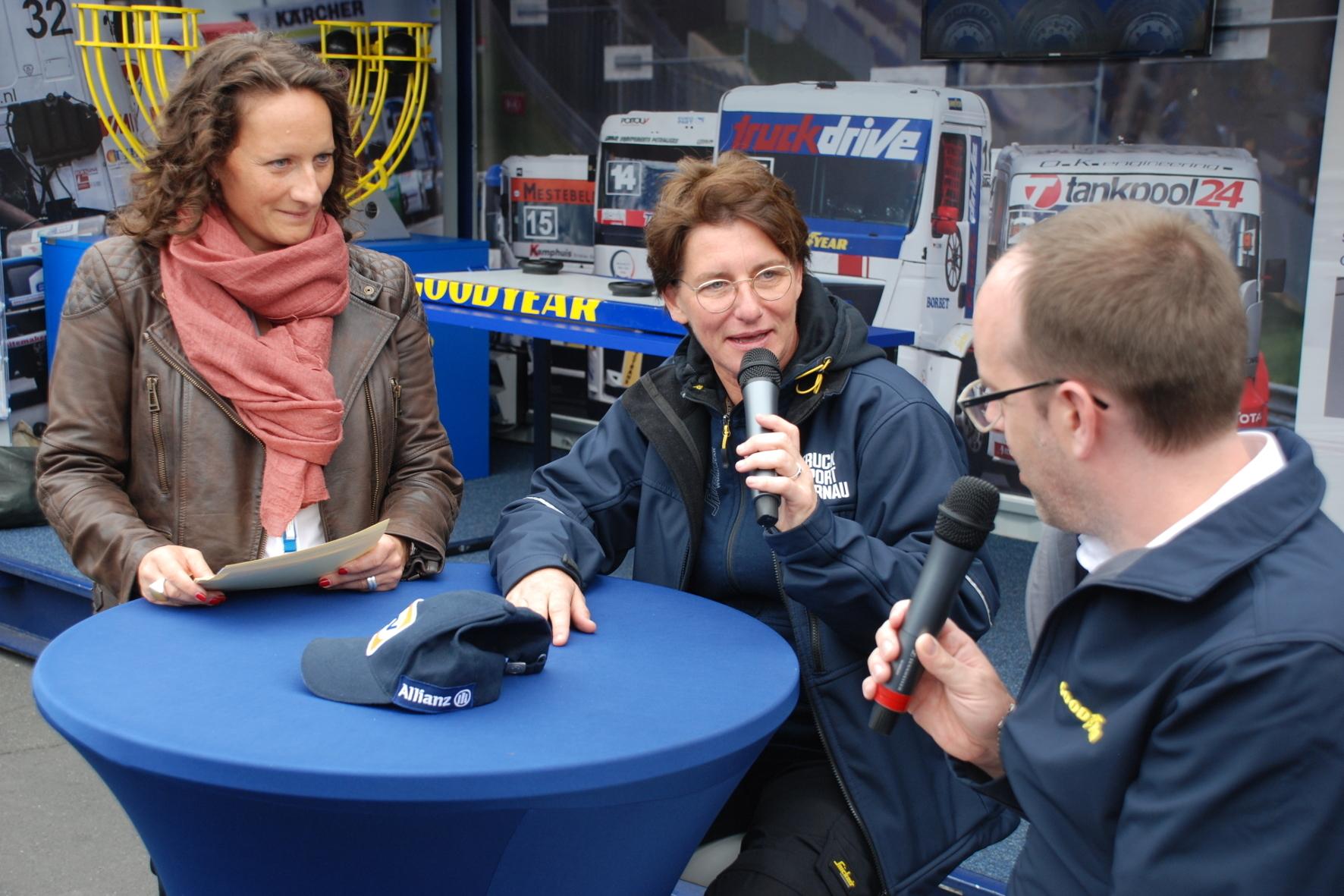 mid Nürburgring - Truck-Rennfahrerin Ellen Lohr (Mitte) schildert ihre Erfahrungen mit Lkw-Reifen. Goodyear-Sprecherin Mirjam Berle und Reifen-Entwickler Daniel Roder hören gespannt zu.