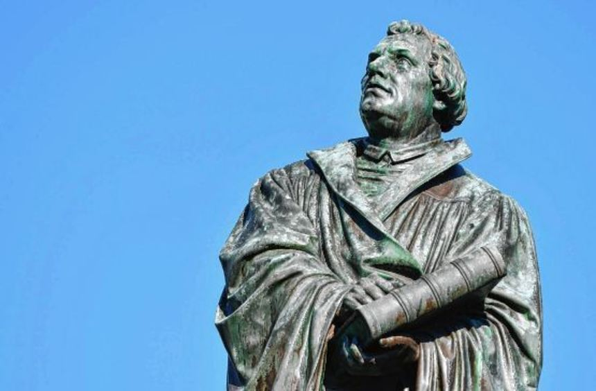 Im Predigtrock gekleidet und mit der Bibel in den Händen steht Martin Luther als Relief aus Bronze ...