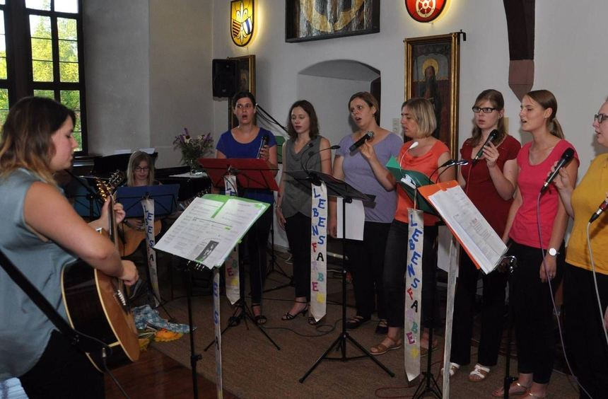 Die Gruppe Lebensfarben mit Chorleiterin Madeleine Wagner beim Auftritt in der Schlossdiele.