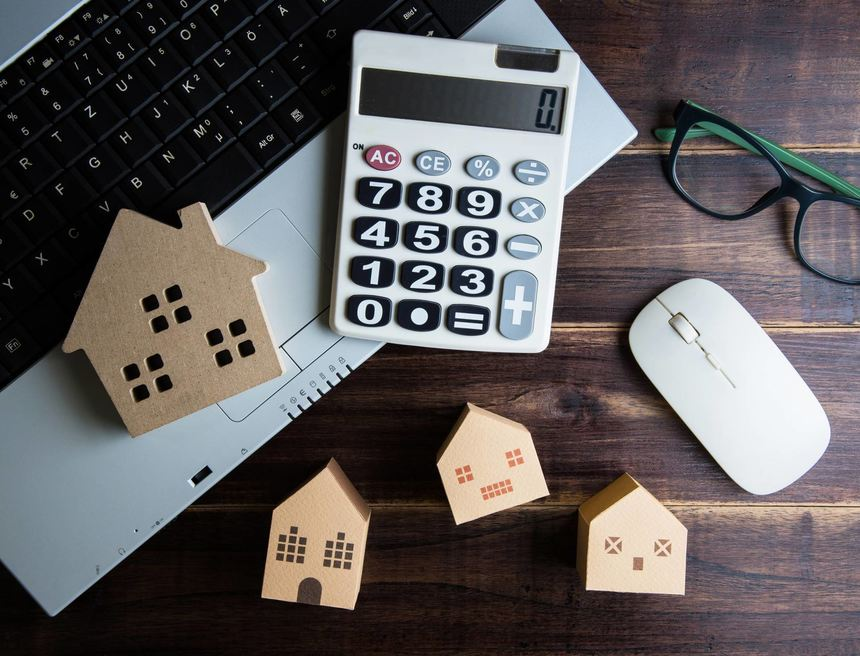 Wooden house, paper house, calculator, glasses and Laptop note book on wooden table background with ...